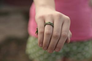 Hand mit aus Gras geflochtenem Ring am Finger